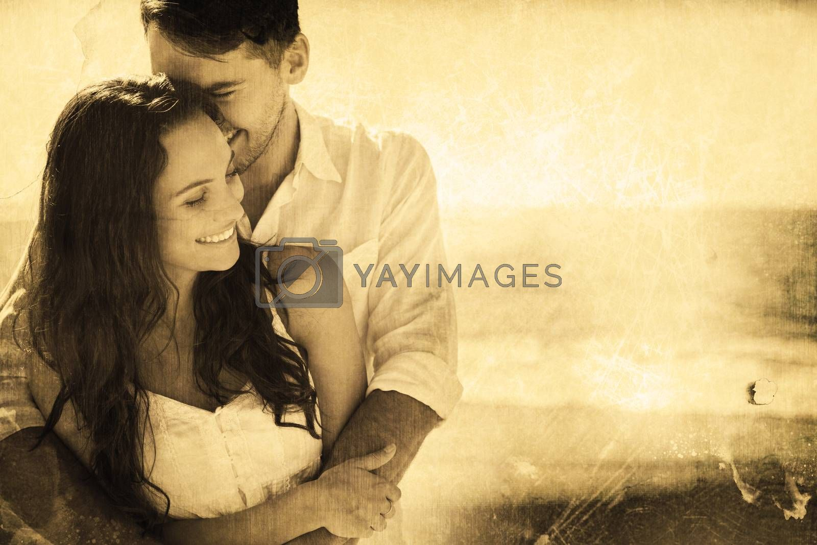 Attractive couple cuddling against grey background