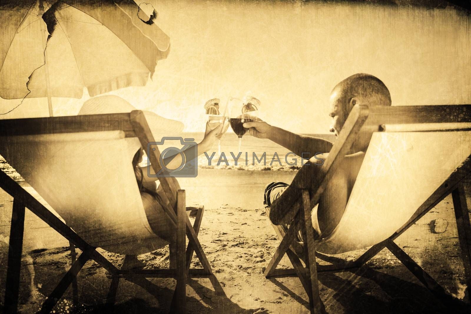 Happy couple clinking their glasses while relaxing on their deck chairs against grey background