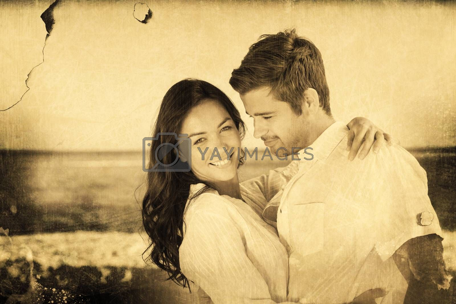 Young couple embracing and posing on the beach  against grey background