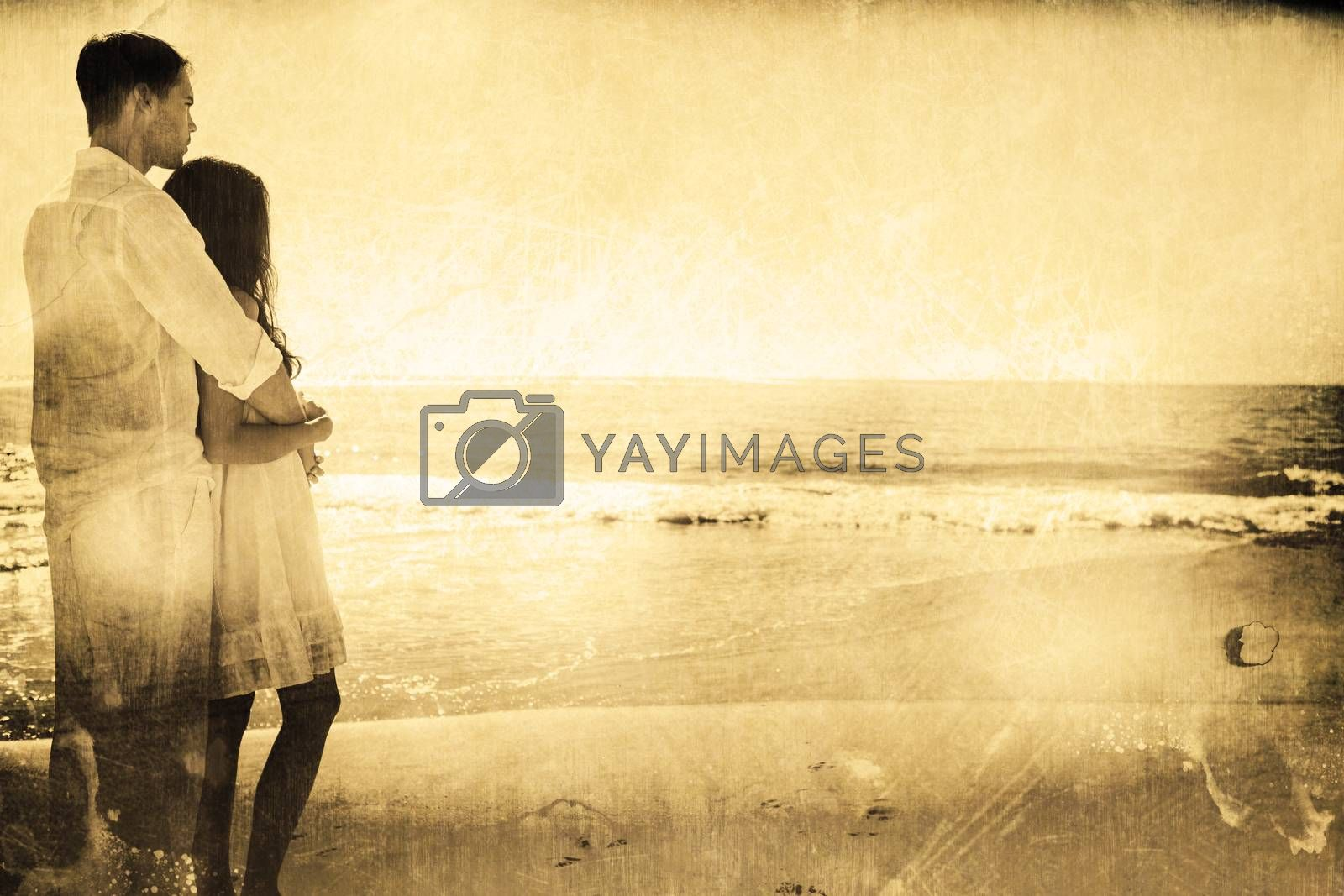 Attractive couple looking out at sea against grey background