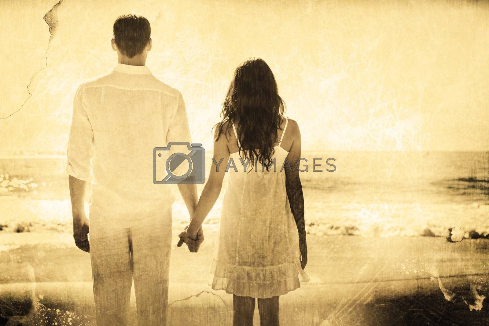 Attractive couple holding hands and watching the ocean against grey background