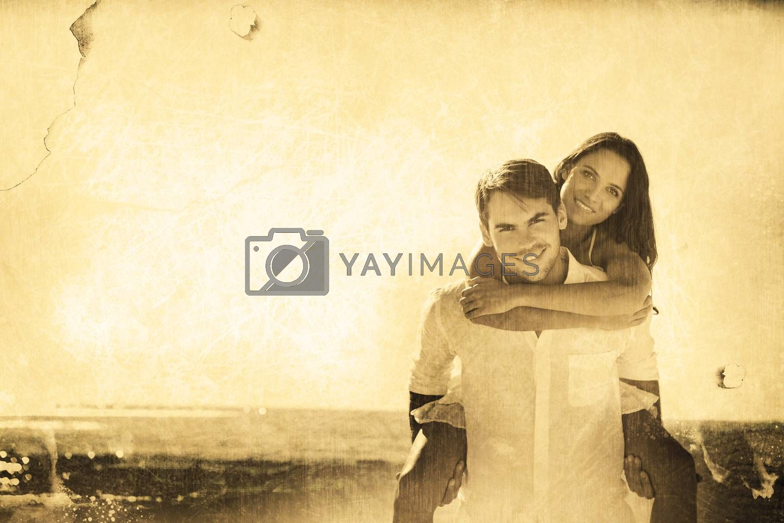 Smiling man giving girlfriend a piggy back looking at camera against grey background