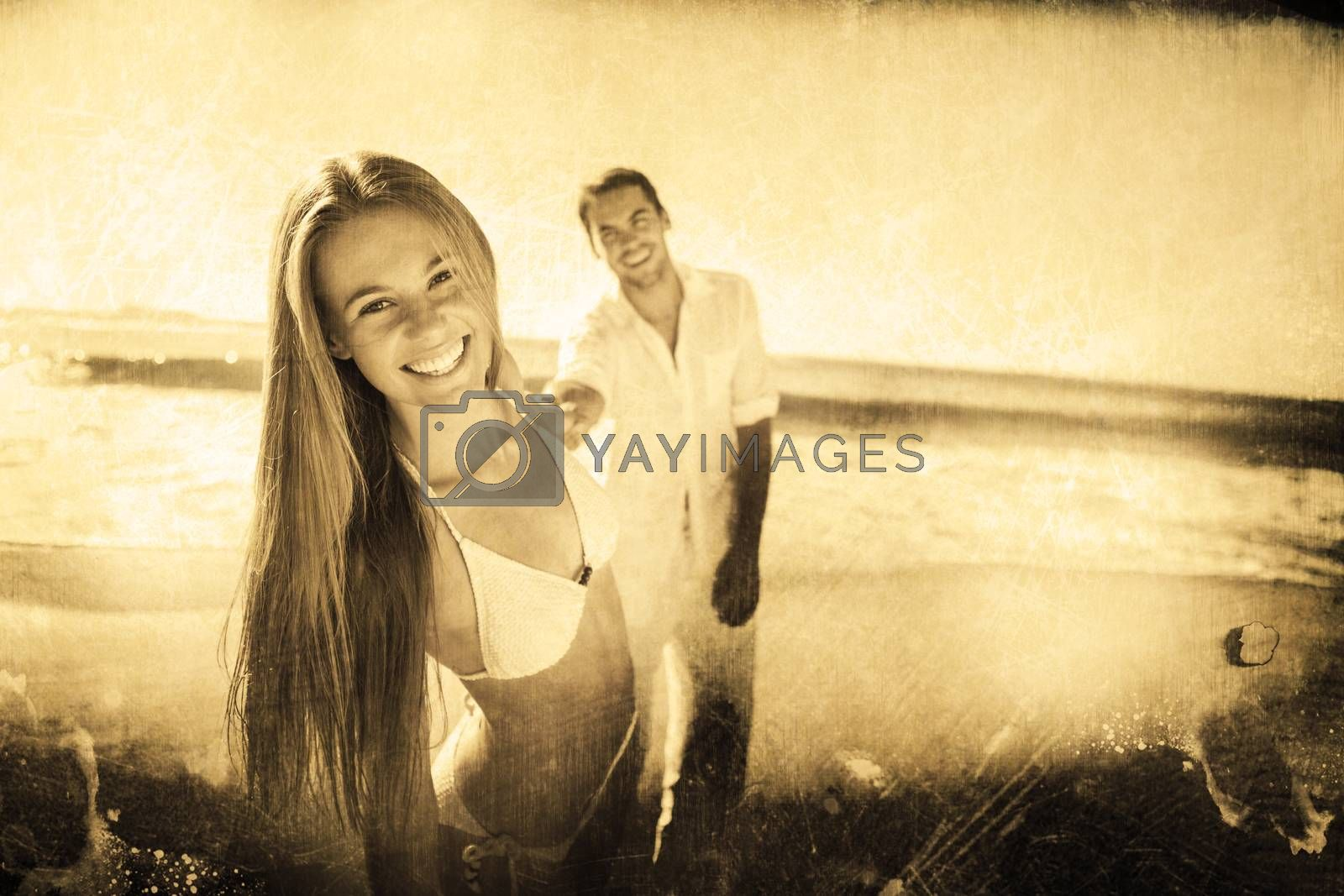 Woman smiling at camera with boyfriend holding her hand against grey background