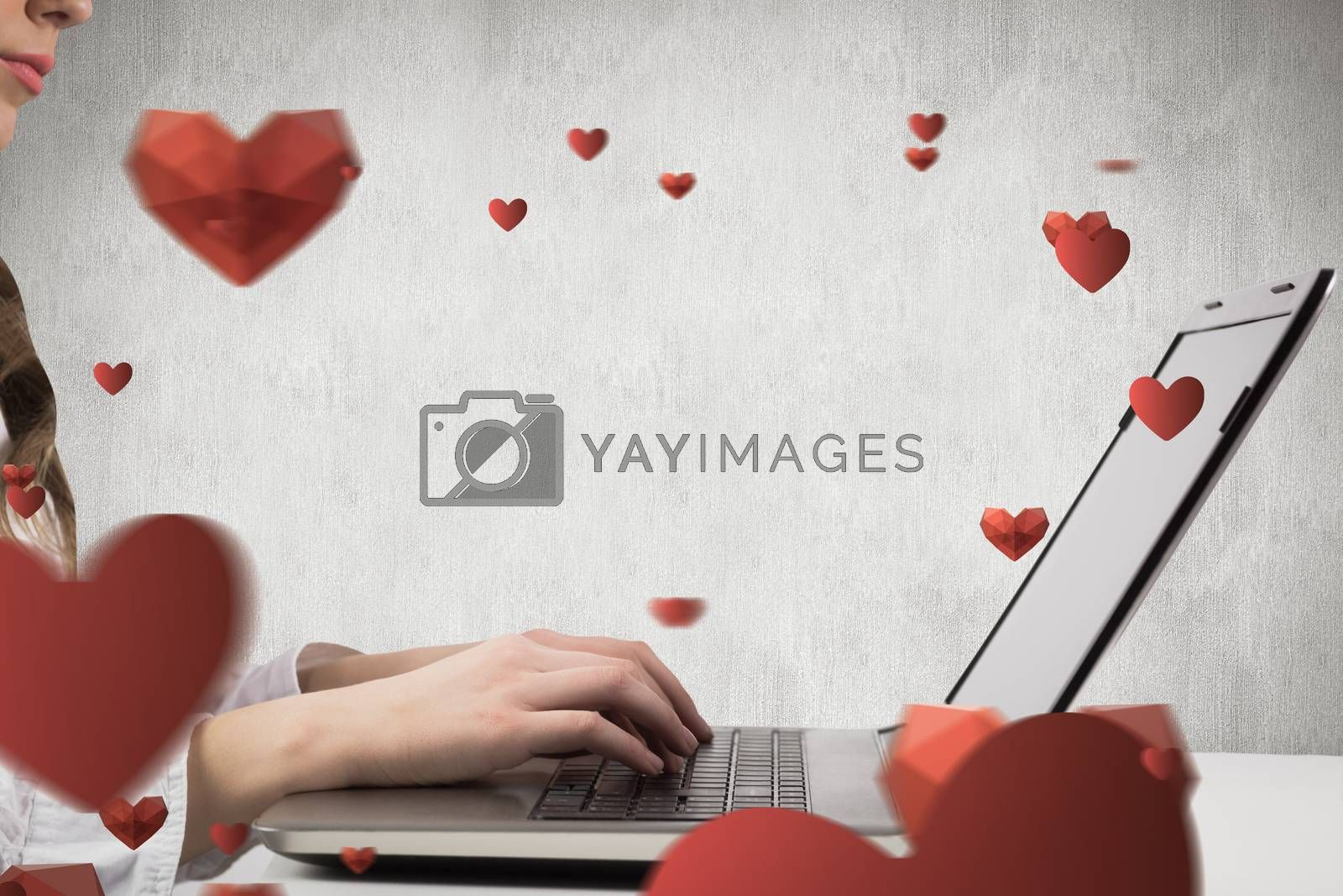 Woman typing on her laptop against white and grey background