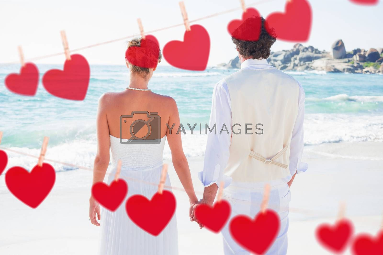 Bride and groom holding hands looking out to sea against hearts hanging on a line