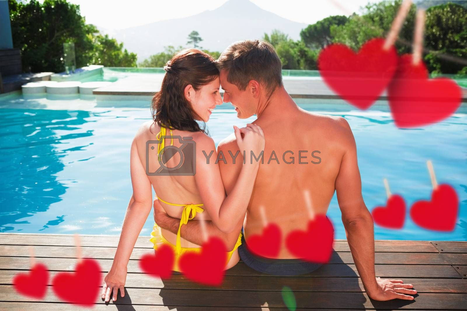 Couple sitting by swimming pool on a sunny day against hearts hanging on a line