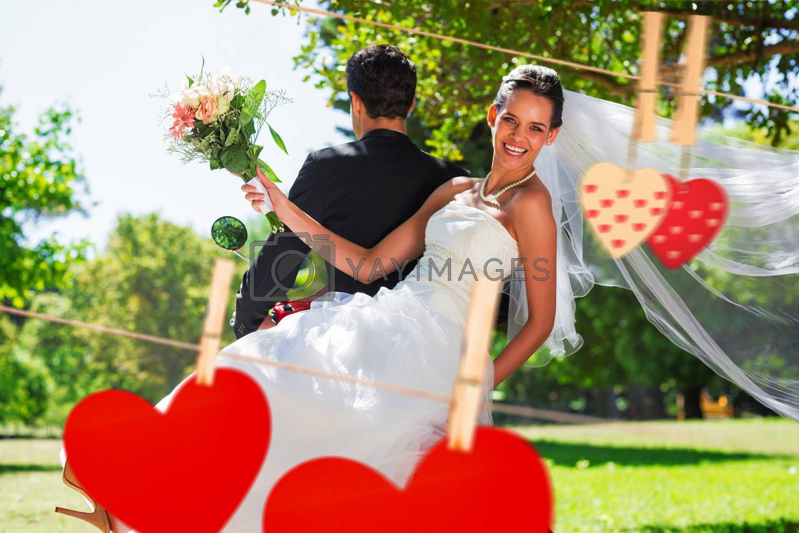 Newlywed couple sitting on scooter in park against hearts hanging on the line