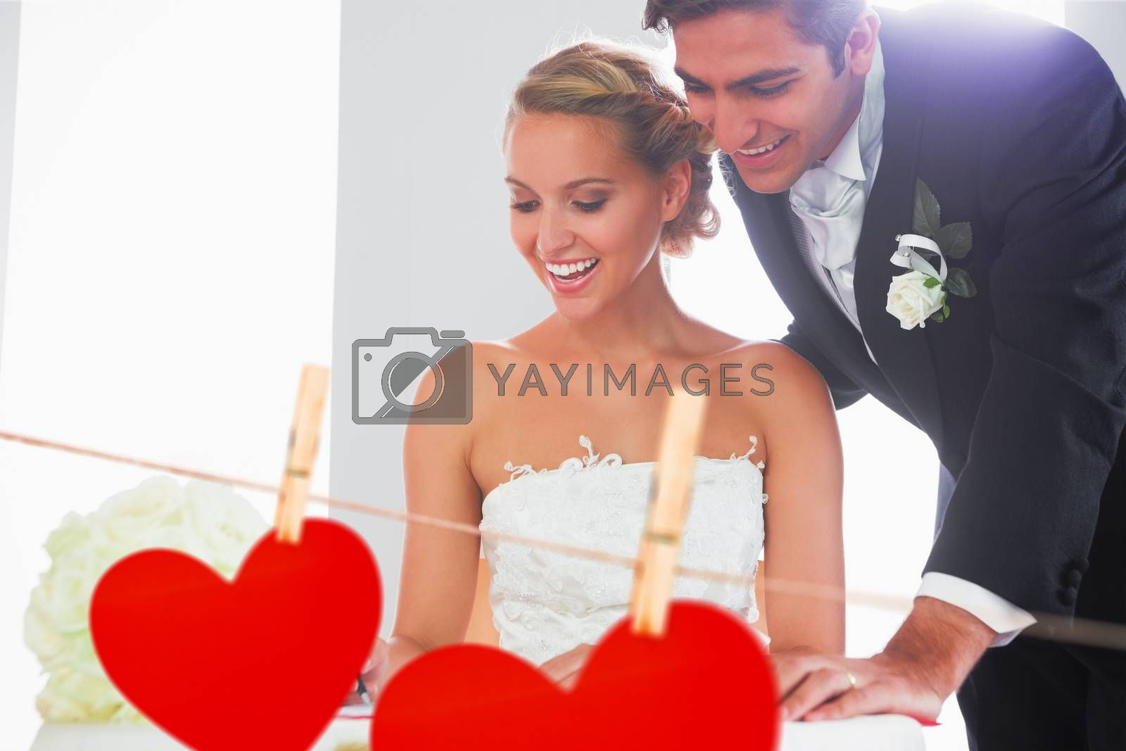Happy young couple signing wedding register against hearts hanging on a line