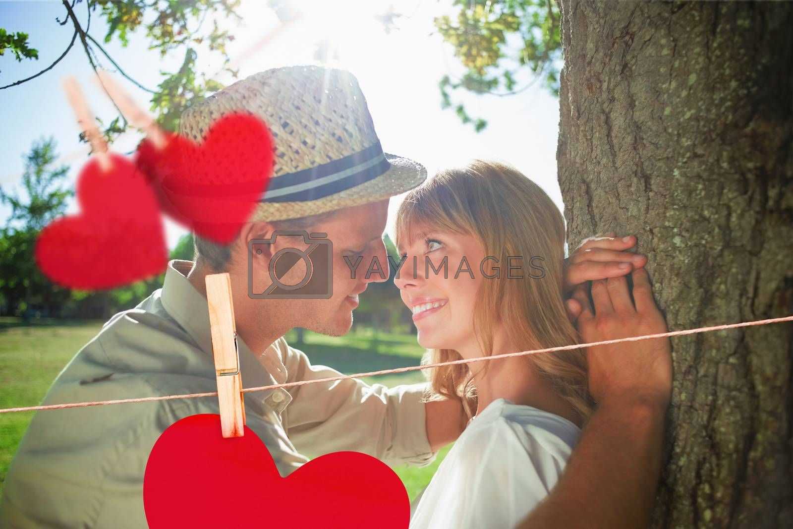 Cute smiling couple leaning against tree in the park against hearts hanging on a line