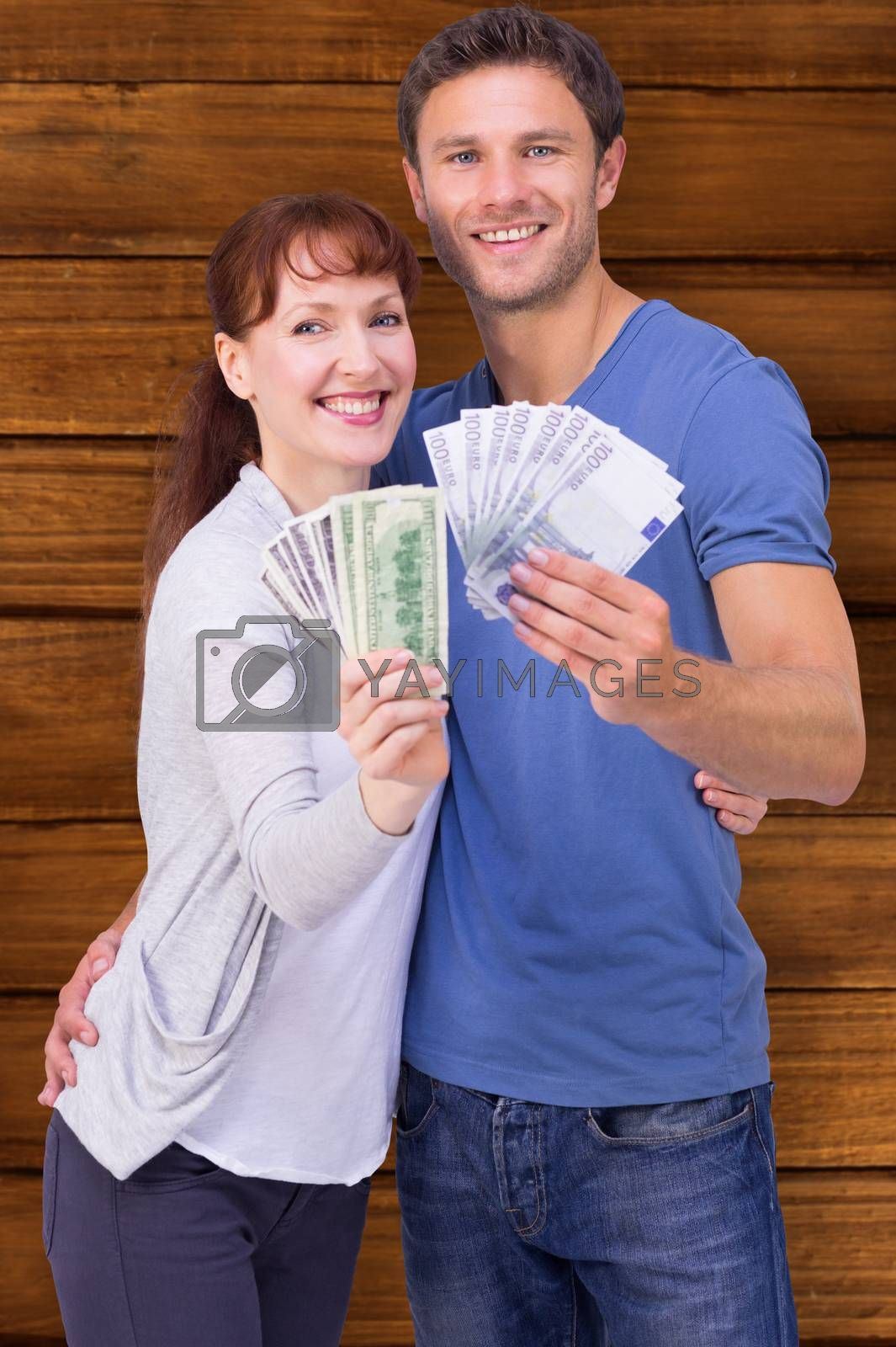 Couple holding fans of cash against wooden planks
