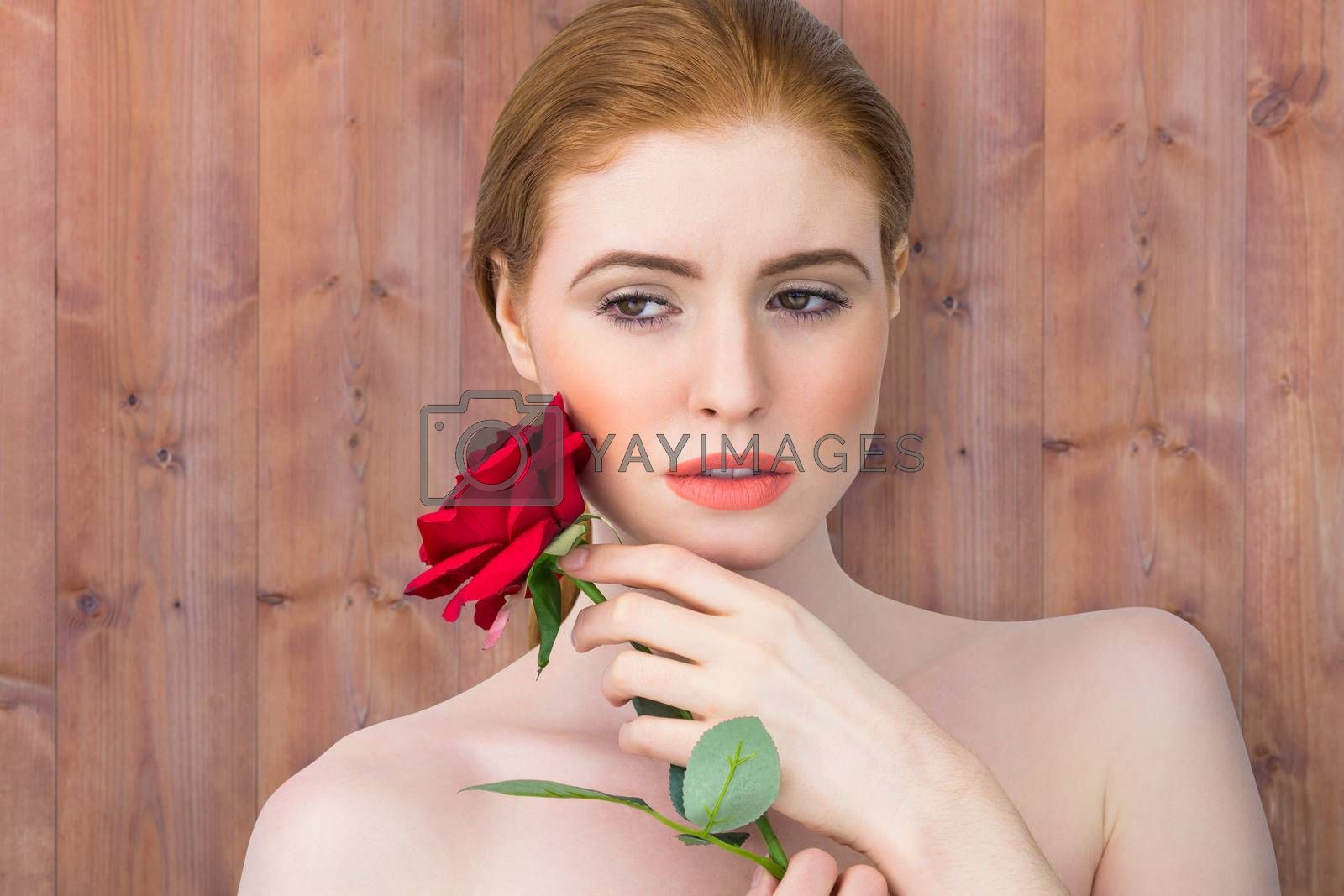 Beautiful redhead posing with red rose against wooden planks