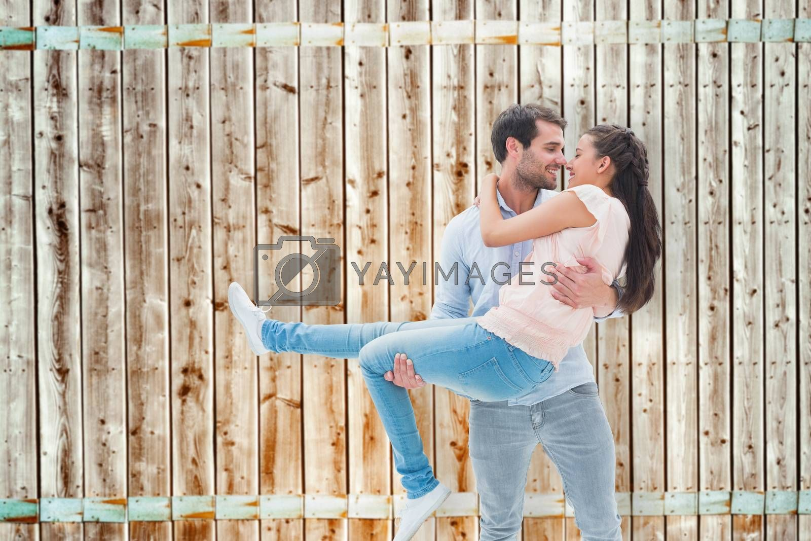 Attractive young couple having fun against wooden background in pale wood