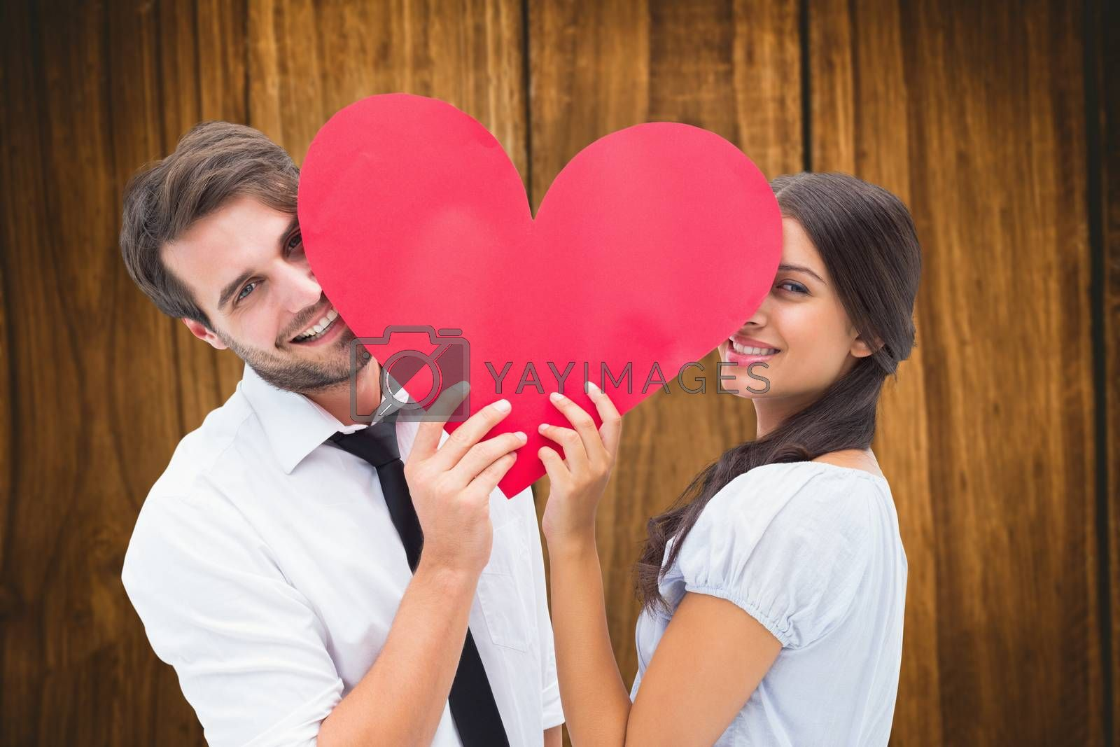 Couple smiling at camera holding a heart against wooden table