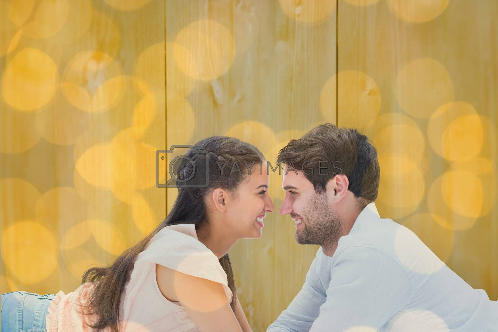 Attractive young couple smiling at each other against blurry yellow christmas light circles