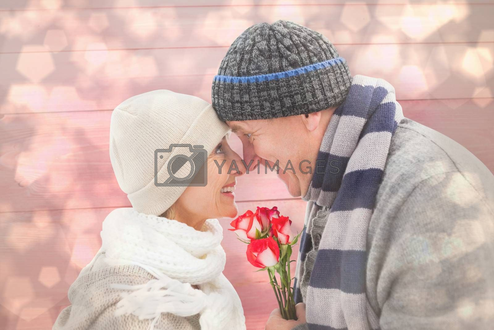 Happy mature couple in winter clothes with roses against light glowing dots design pattern