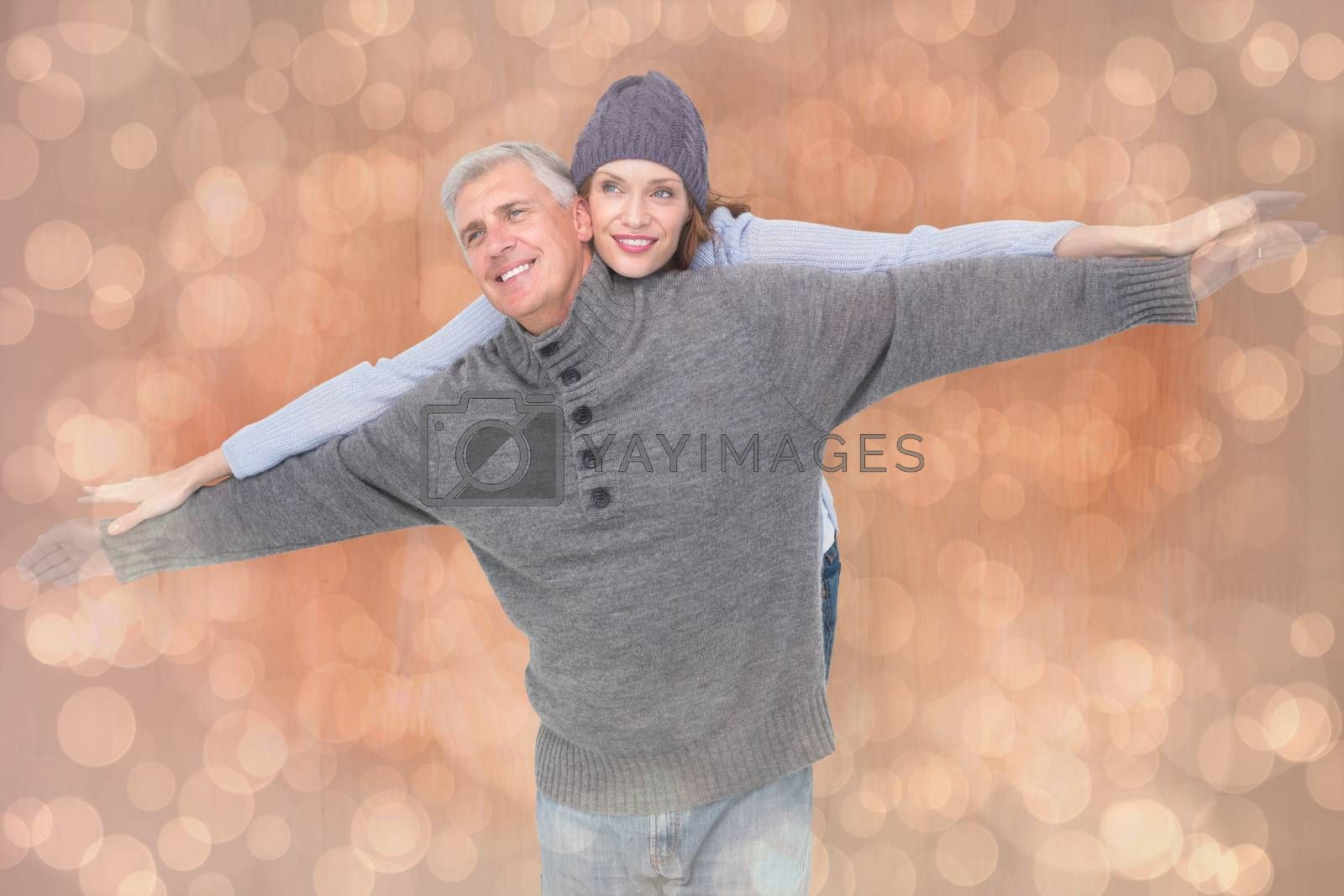 Carefree couple in warm clothing against light glowing dots design pattern