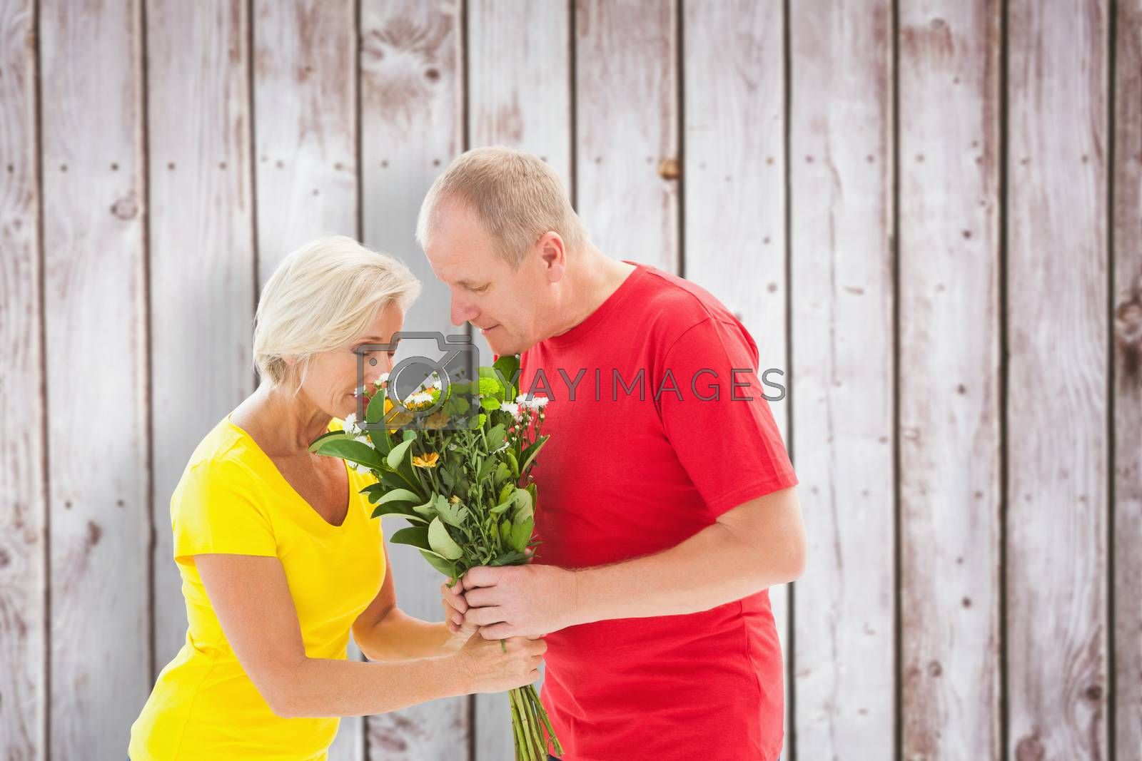 Mature man offering his partner flowers against wooden planks