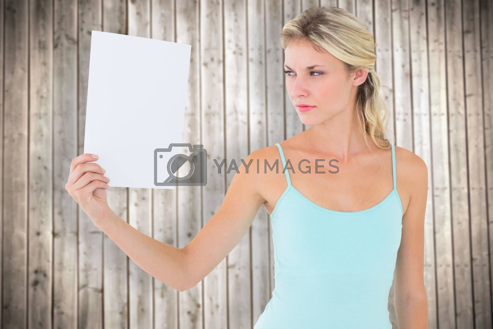 Angry blonde holding a sheet of paper against wooden planks background
