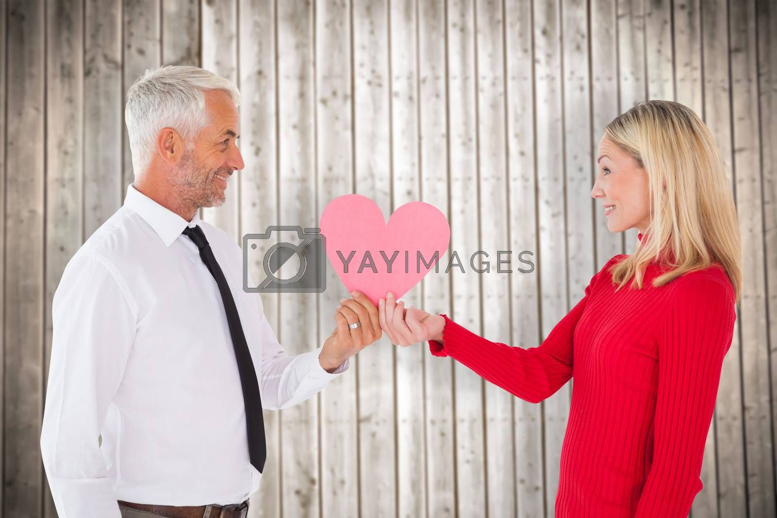 Handsome man getting a heart card form wife against wooden planks background