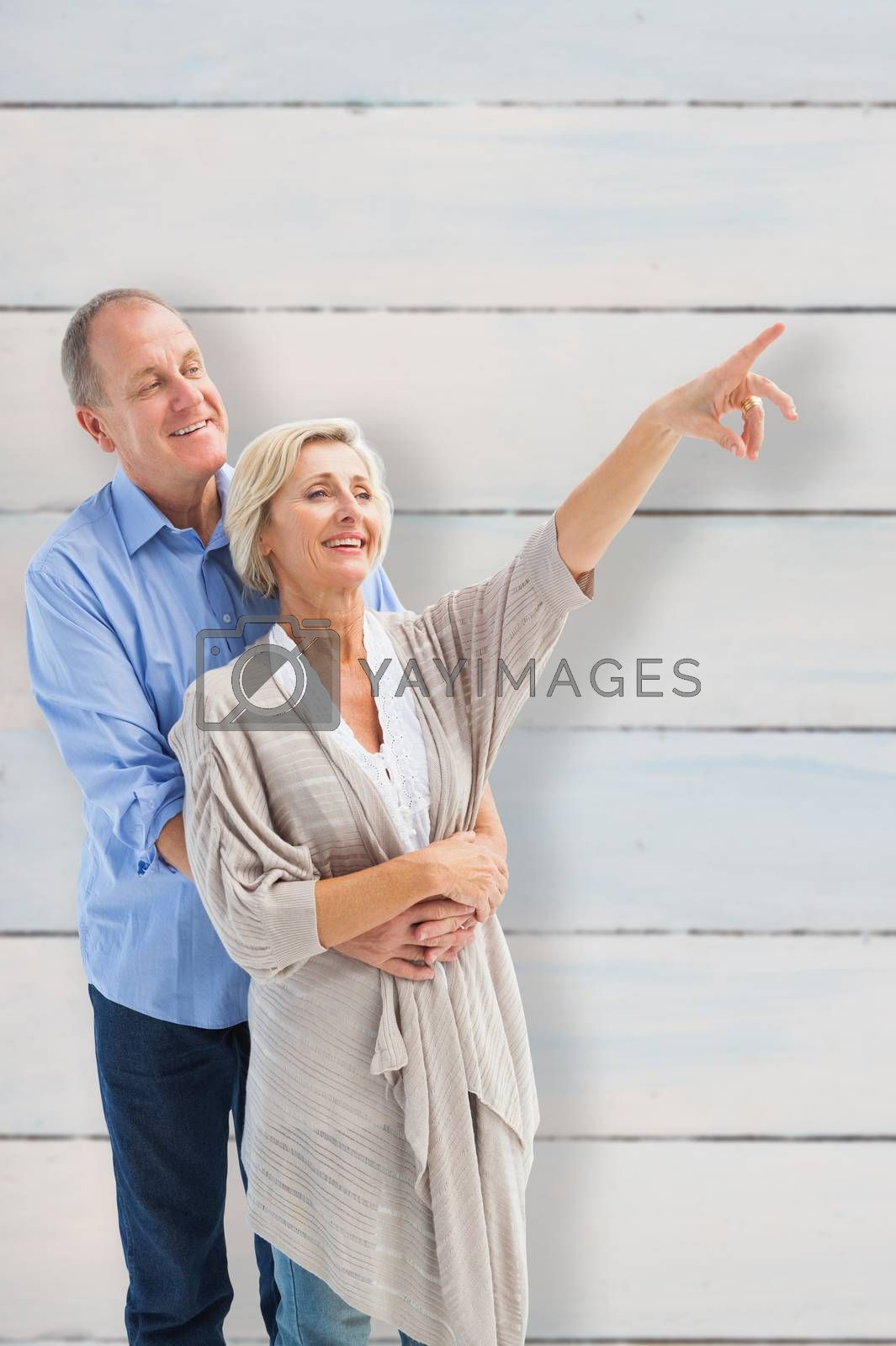 Happy mature couple embracing and looking against wooden planks