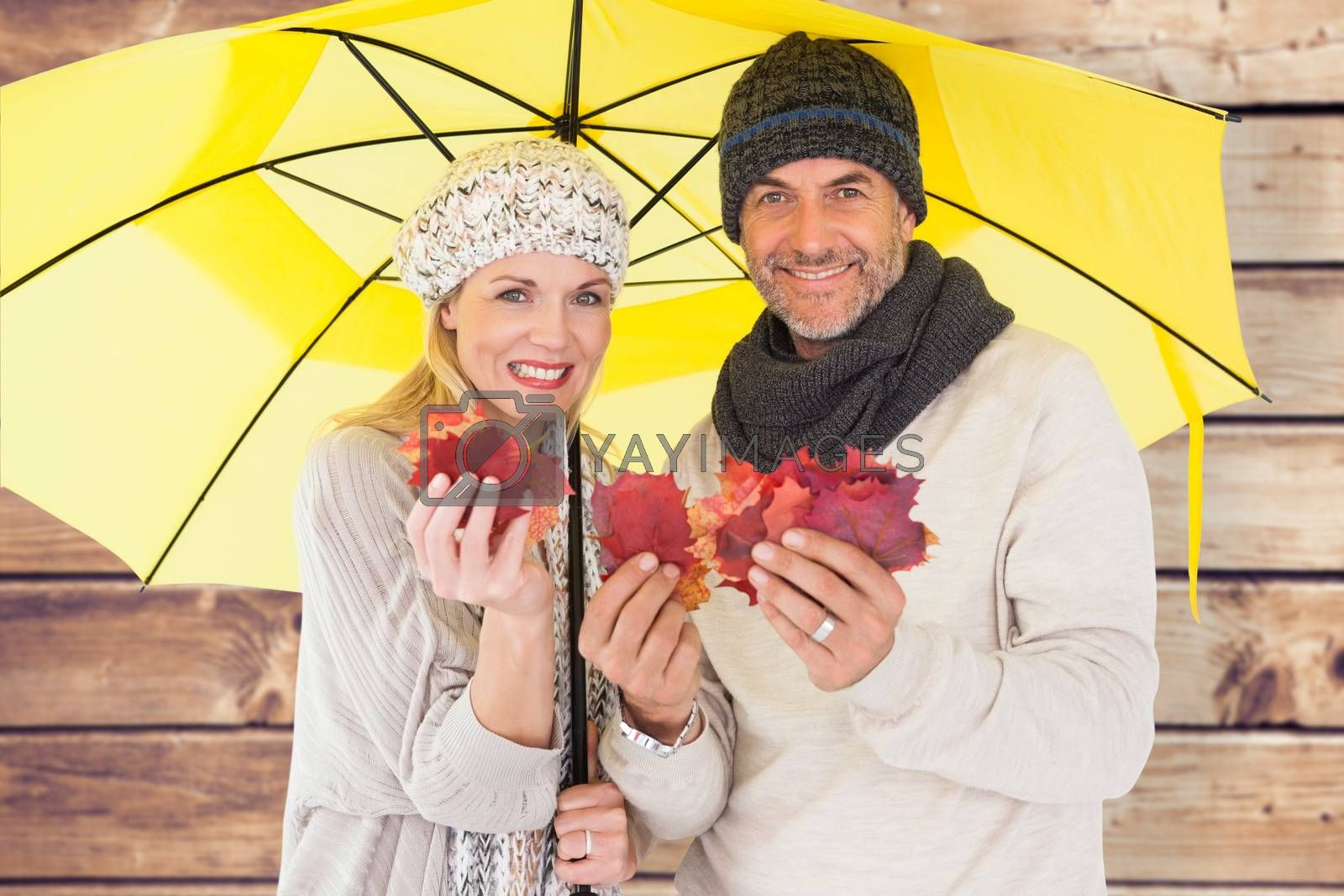 Couple in winter fashion showing autumn leaves under umbrella against wooden planks background