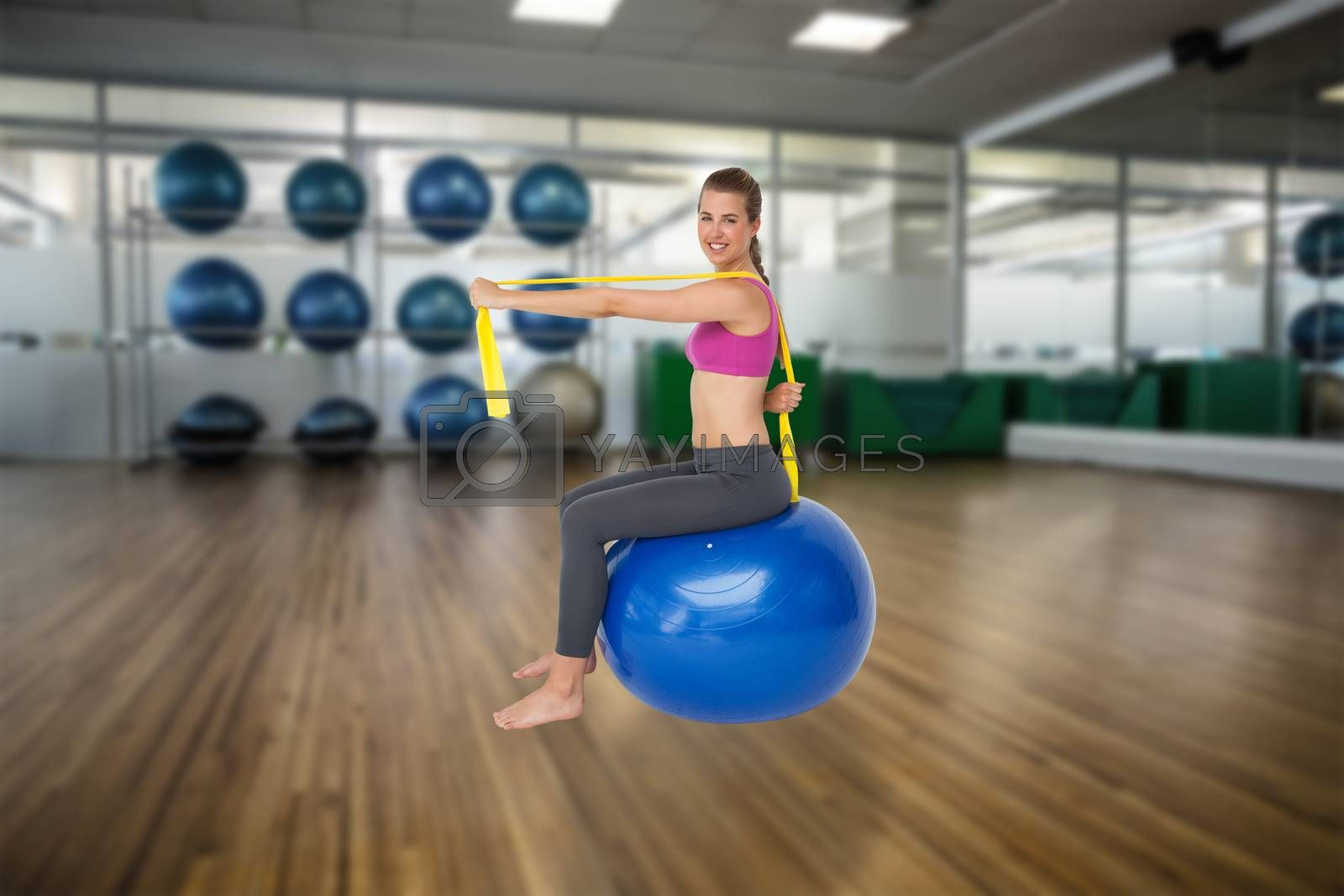 Full length portrait of fit woman exercising on fitness ball against large empty fitness studio with shelf of exercise balls