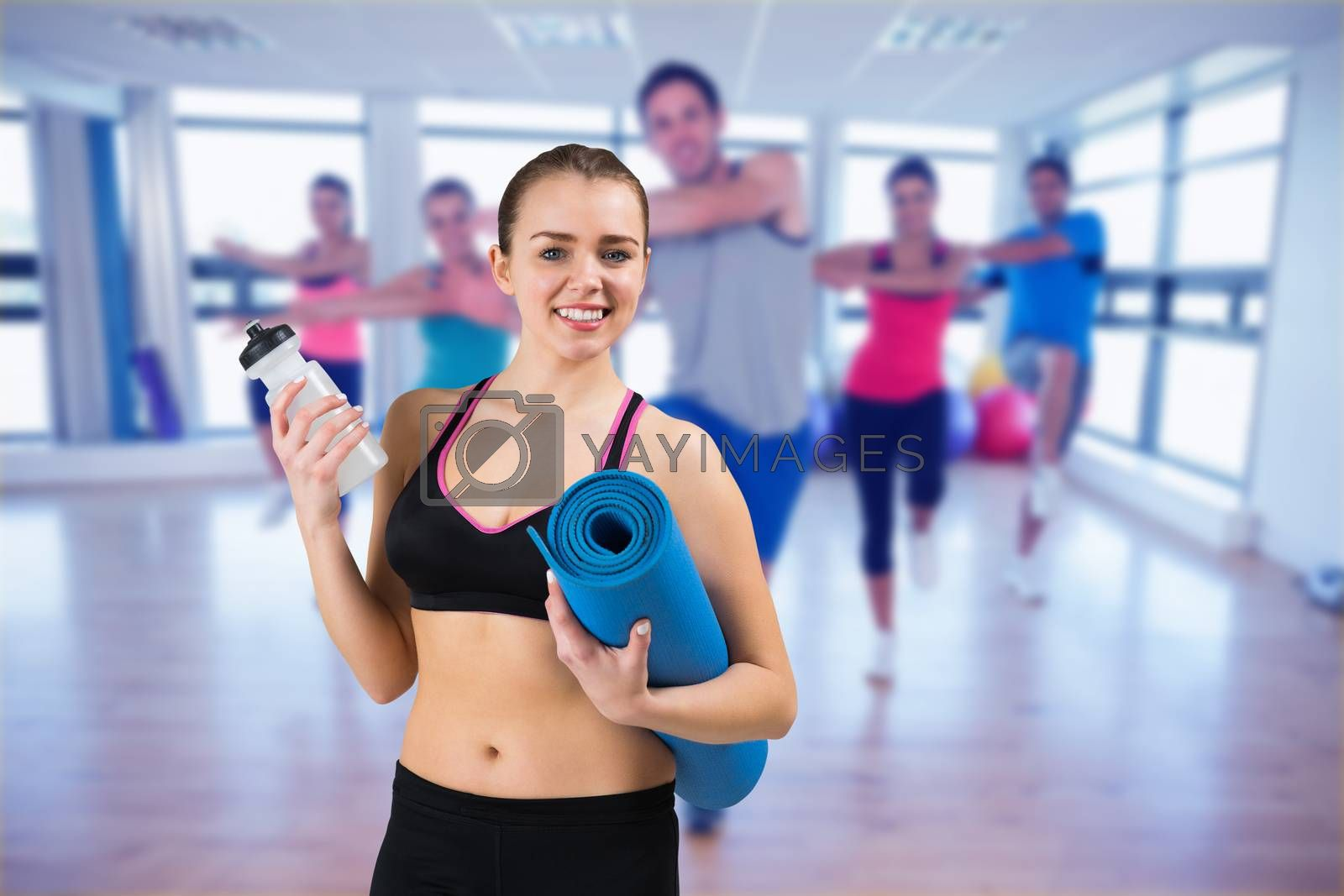 Composite image of fit brunette holding mat and sports bottle