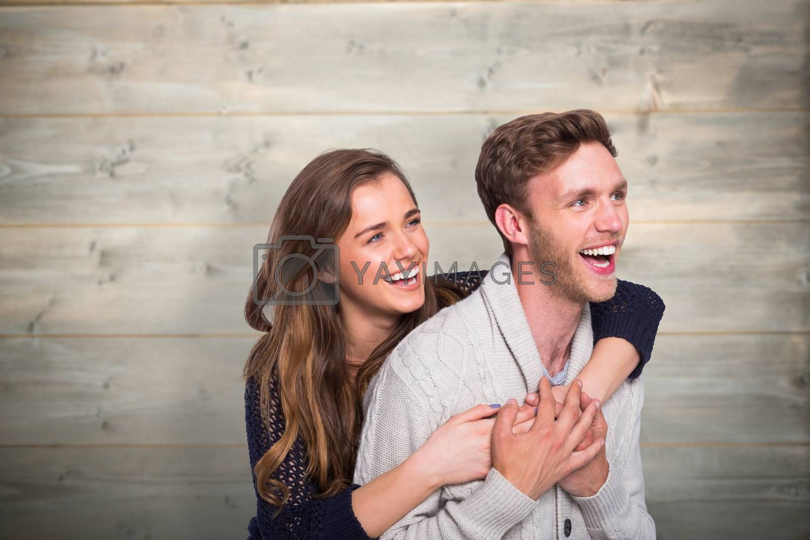 Cheerful young couple embracing against bleached wooden planks background