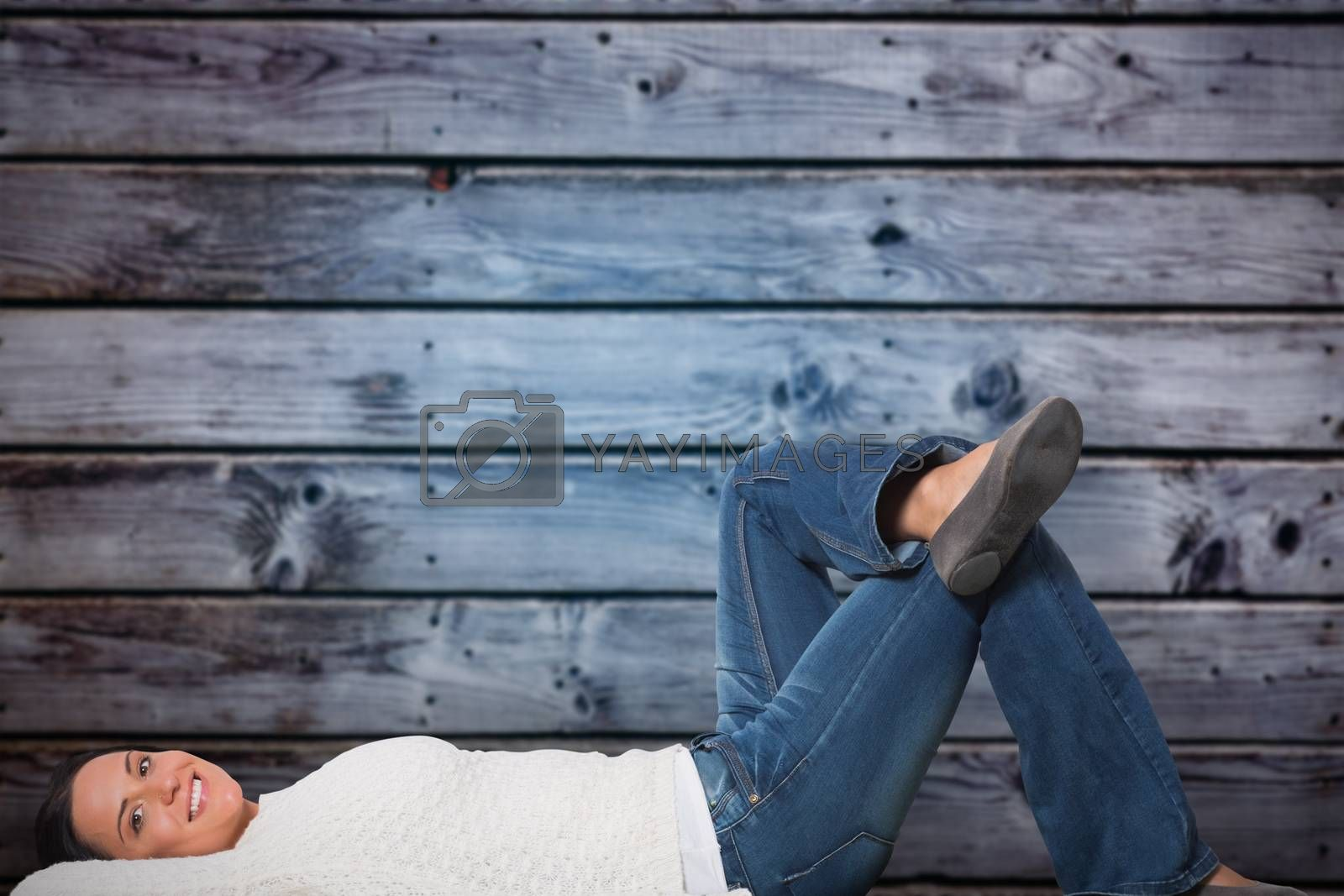 Young woman lying on floor smiling against grey wooden planks