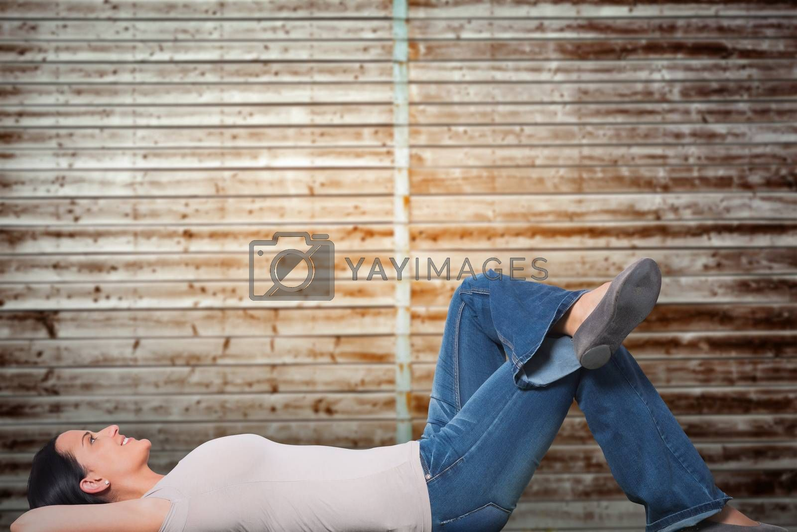 Young woman lying on floor thinking against wooden planks