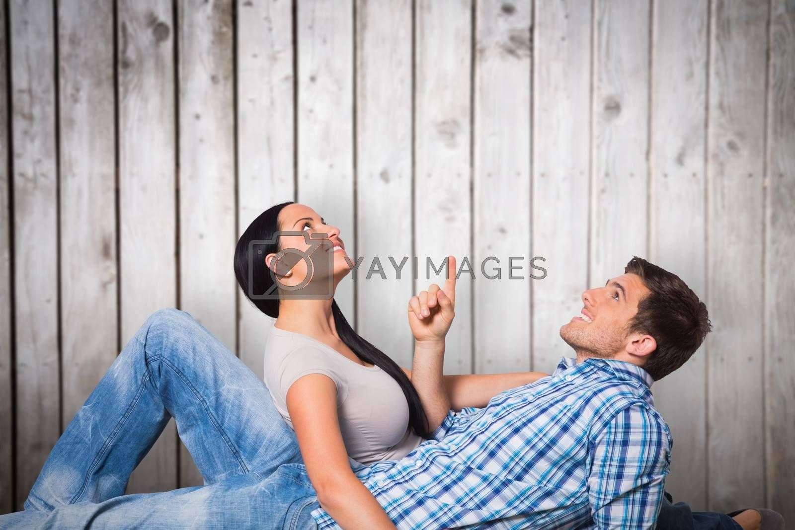 Young couple lying on floor smiling against wooden planks