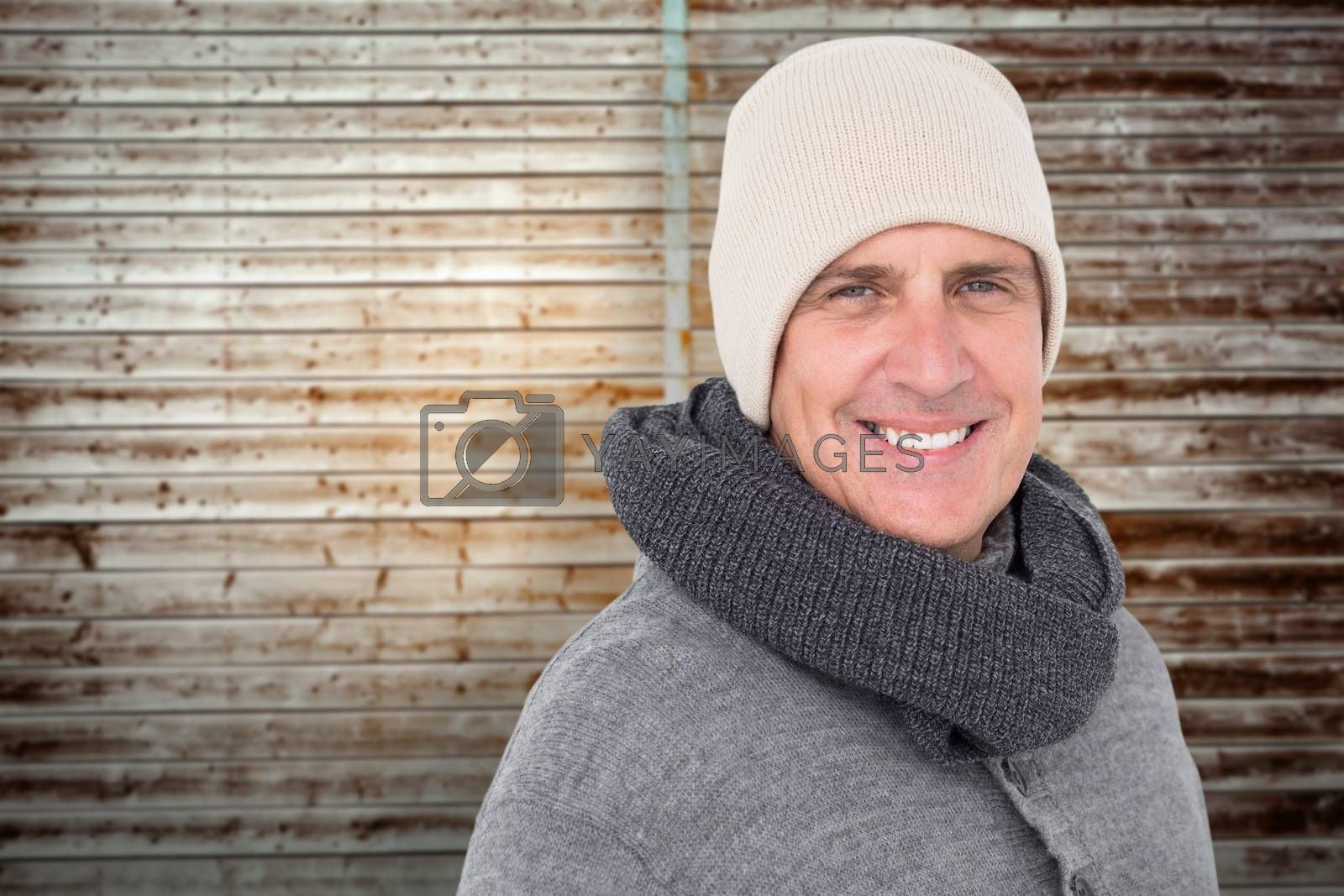 Casual man in warm clothing against wooden planks