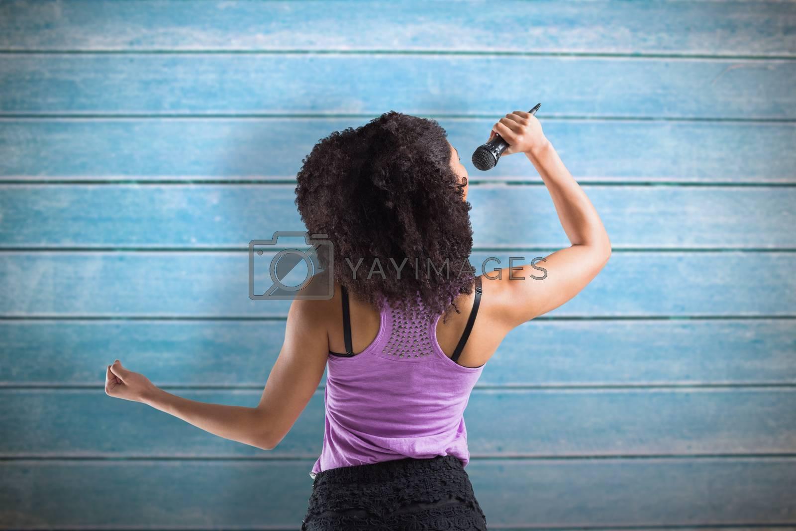 Pretty girl singing against wooden planks