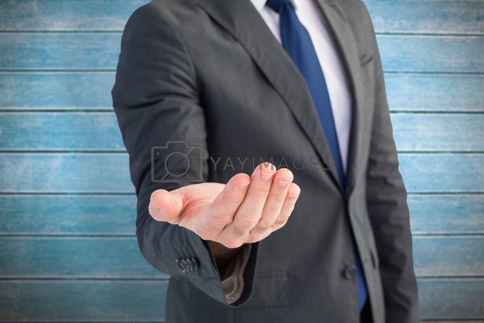 Businessman holding out his hand against wooden planks
