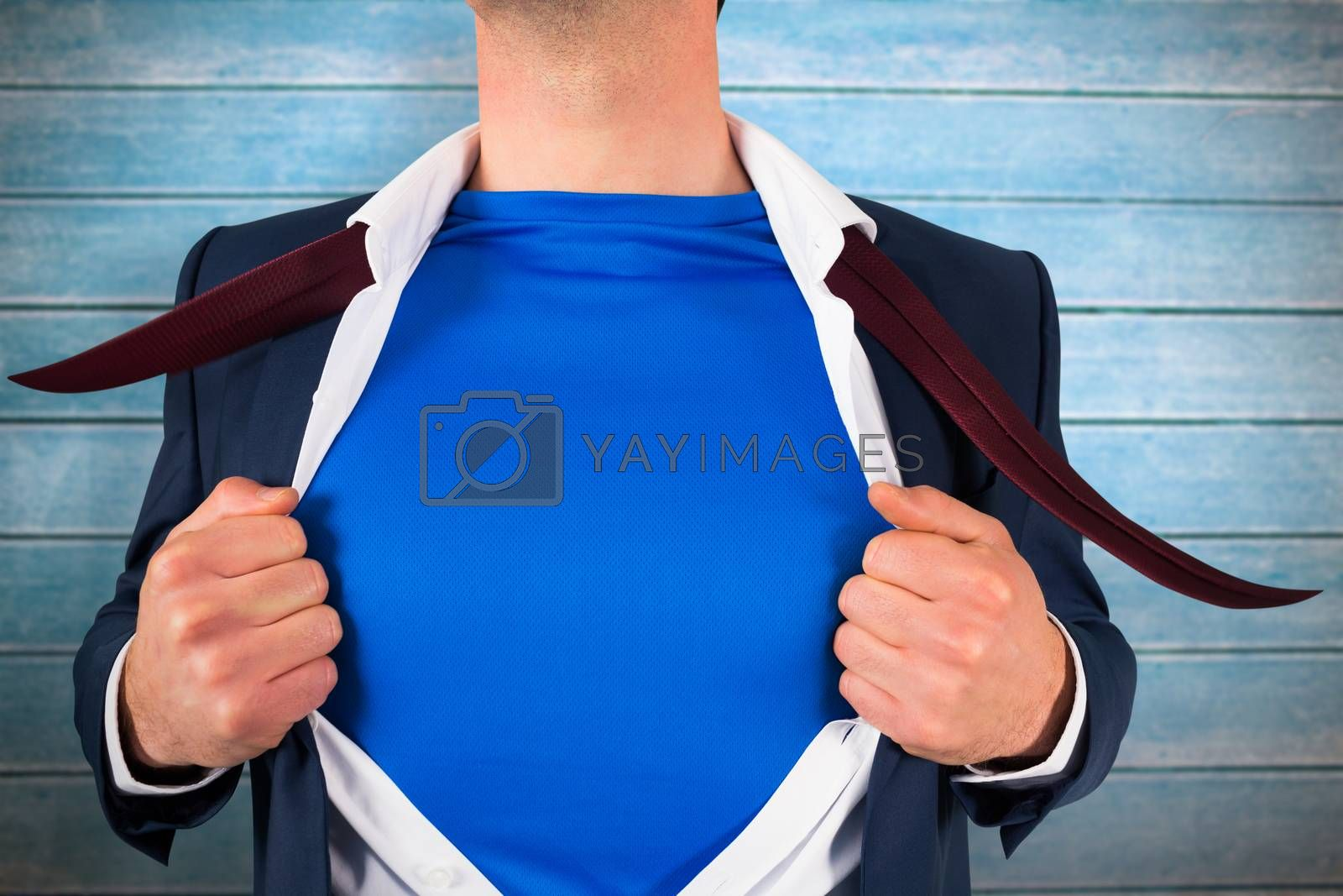 Businessman opening his shirt superhero style against wooden planks
