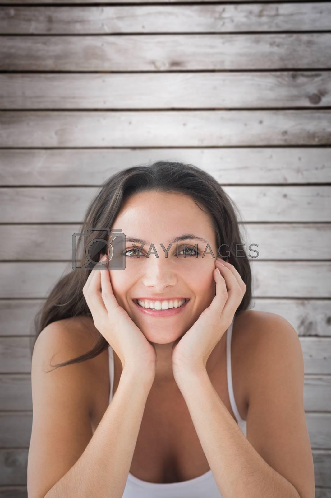 Smiling brunette against wooden planks