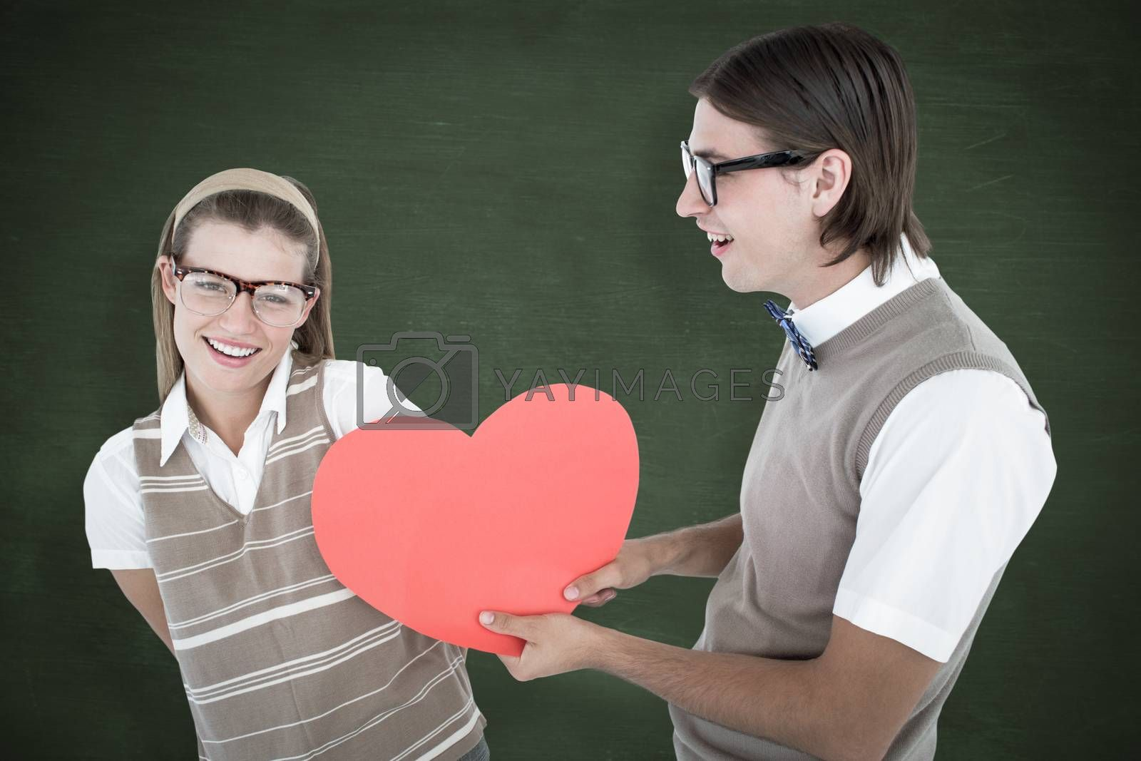 Geeky hipster offering red heart to his girlfriend  against green chalkboard