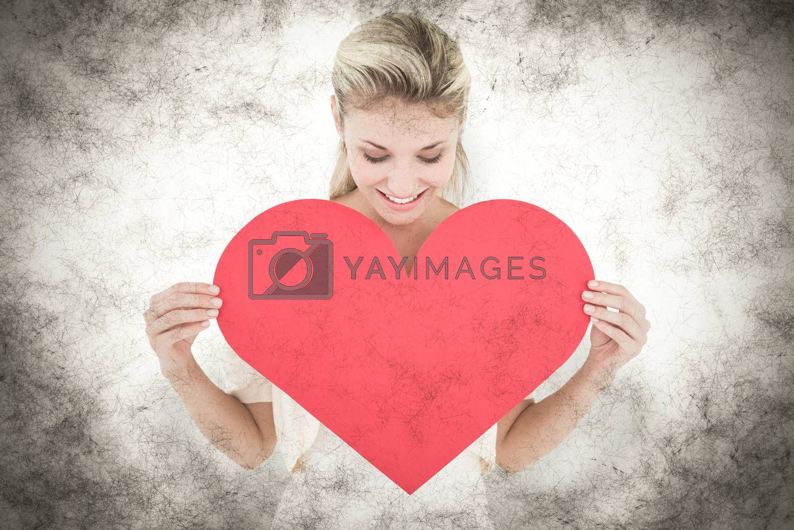 Attractive young blonde showing red heart against grey background