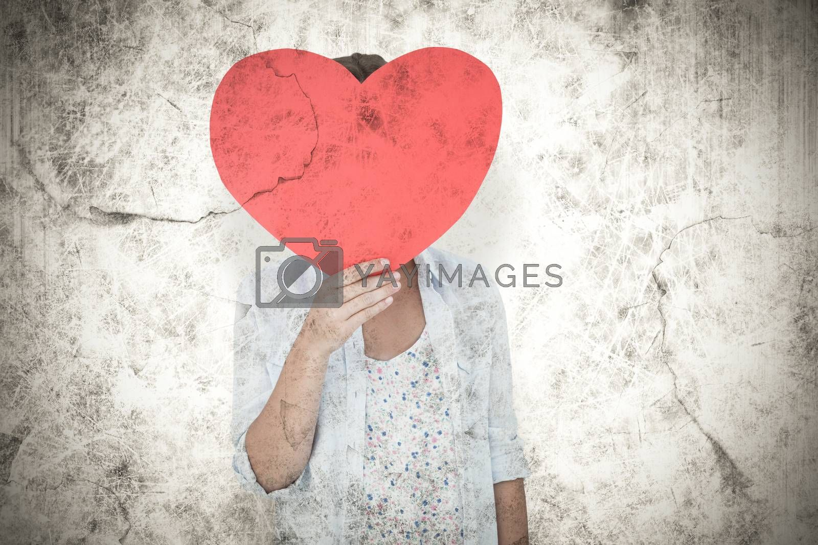 Woman holding heart card  against grey background