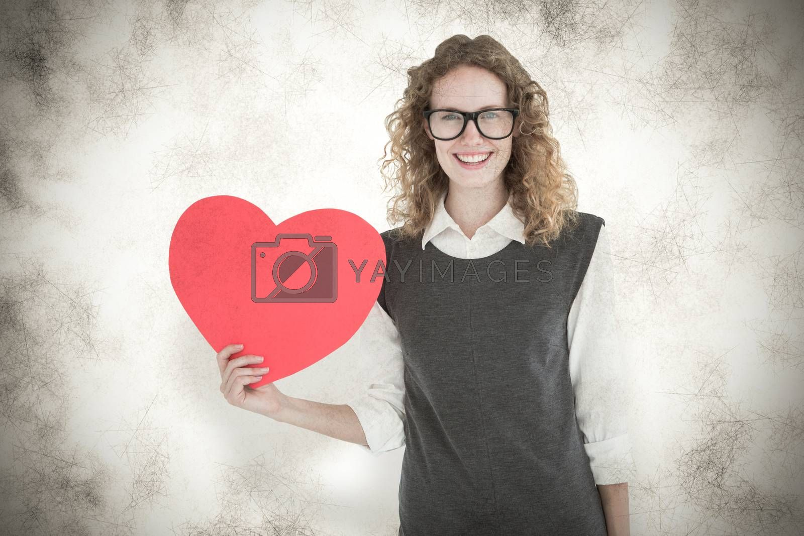 Geeky hipster holding heart card against grey background