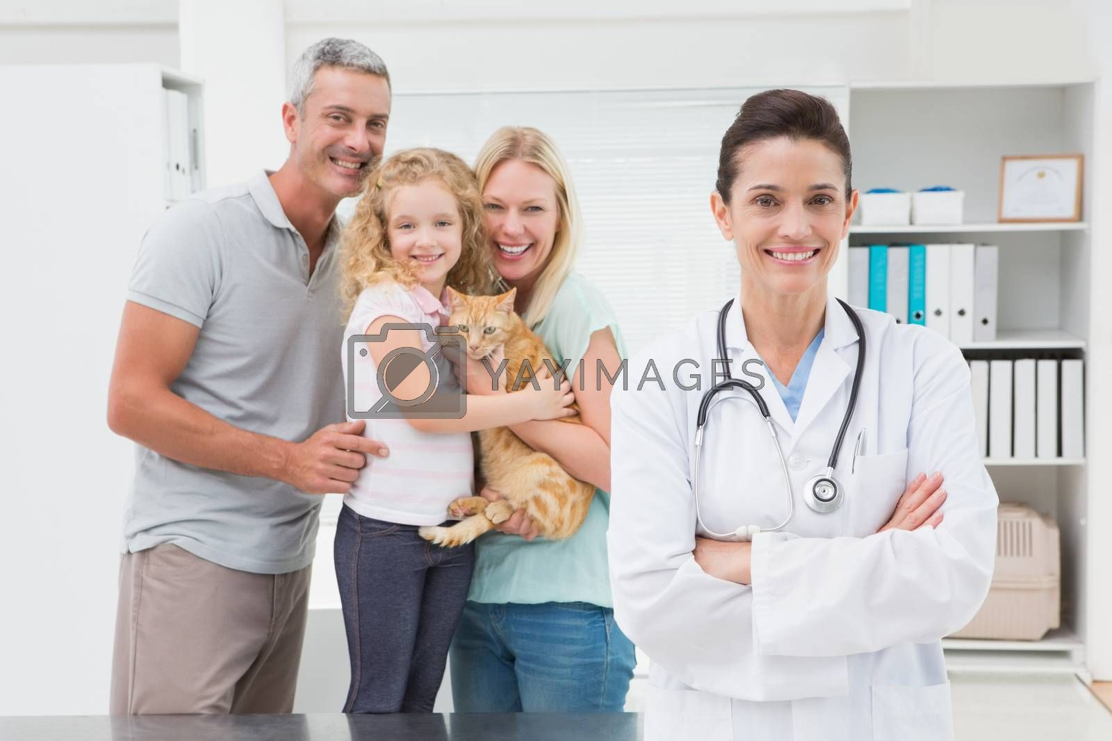 Veterinarian and cat owners smiling at camera in medical office