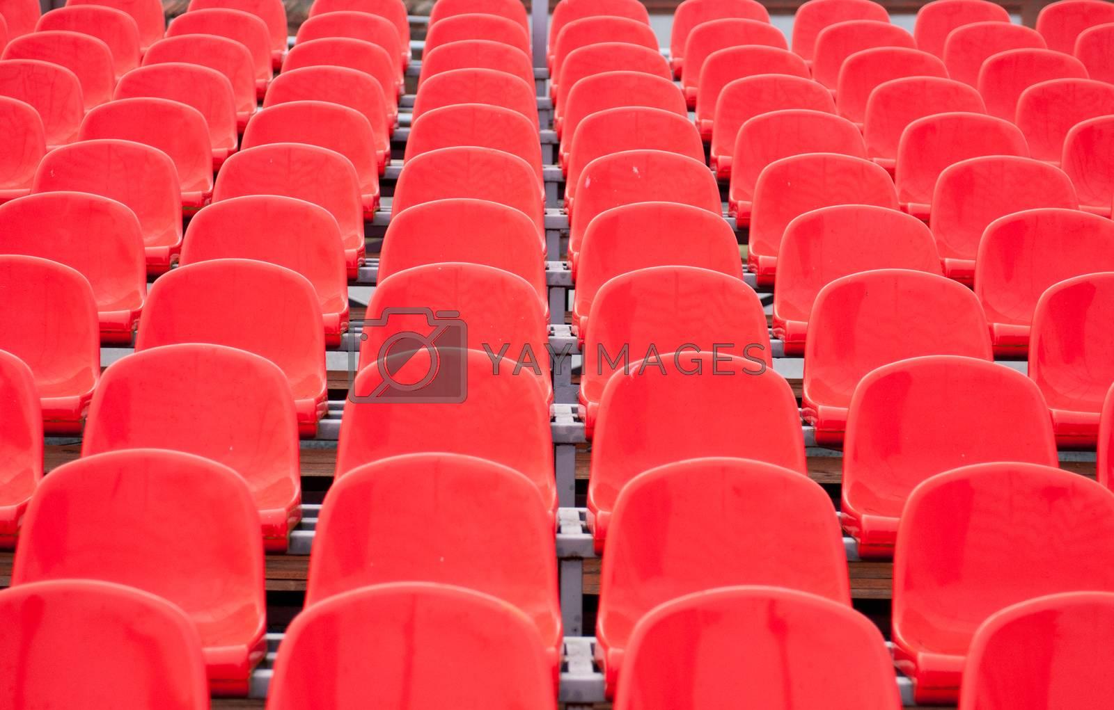 Empty bright red plastic seats in a stadium.