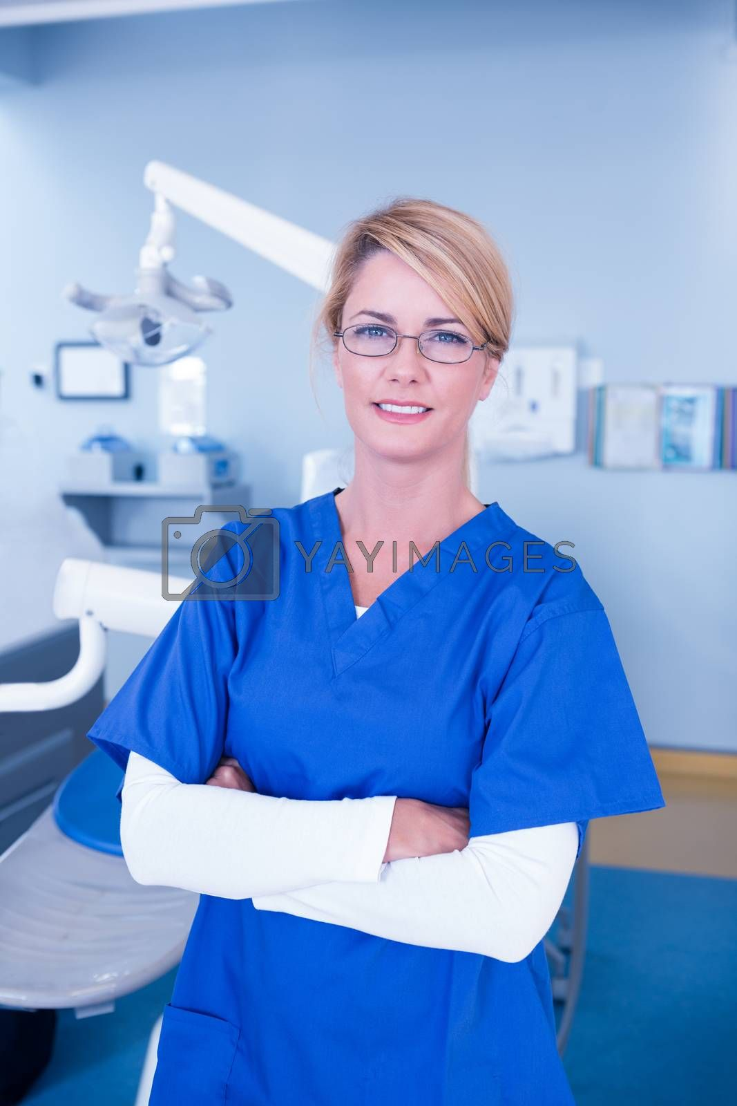 Dentist smiling at camera with arms crossed at the dental clinic