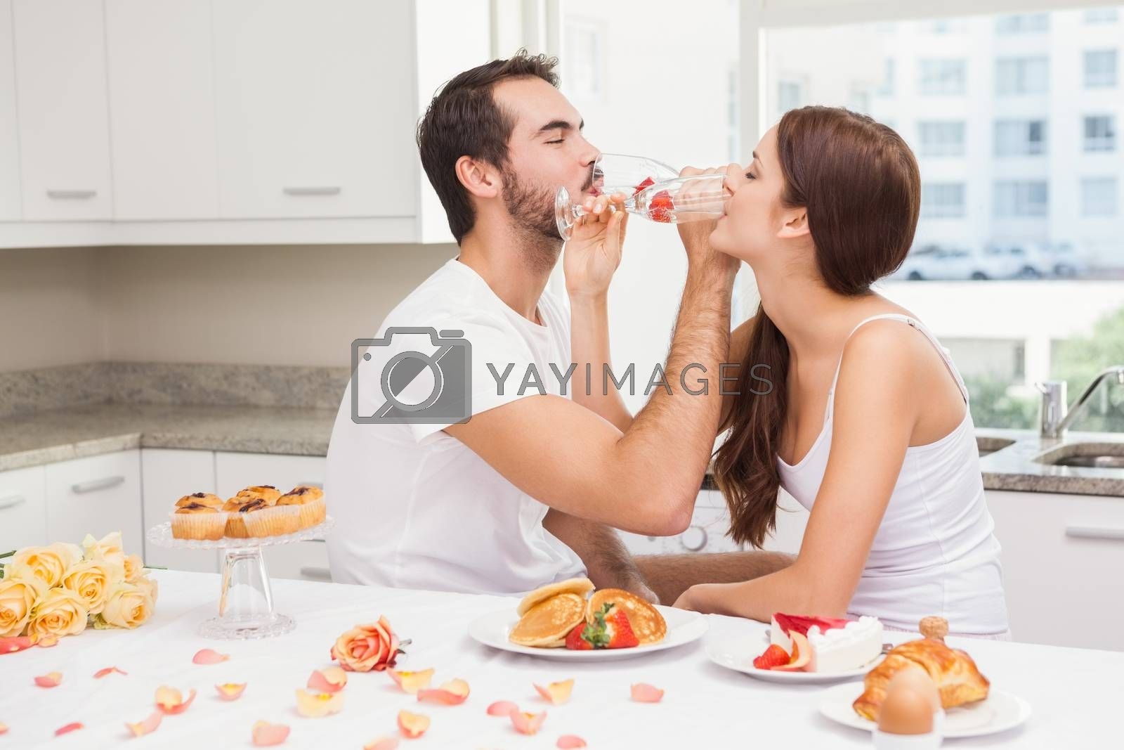 Cut couple drinking champagne together at home in the kitchen