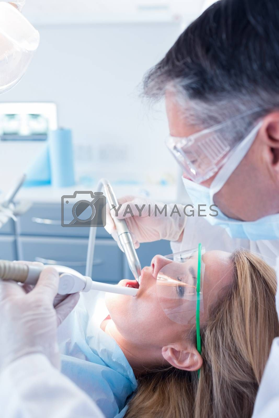 Dentist examining his patient with a suction hose at the dental clinic