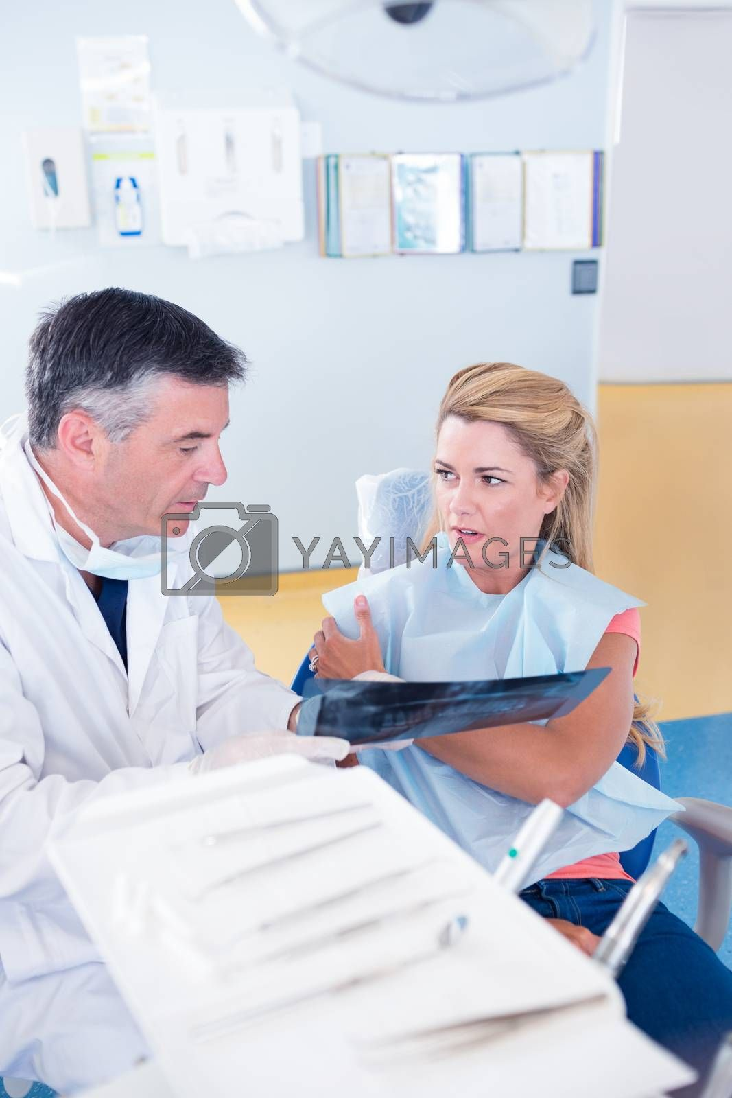 Dentist discussing x-ray with his patient at the dental clinic