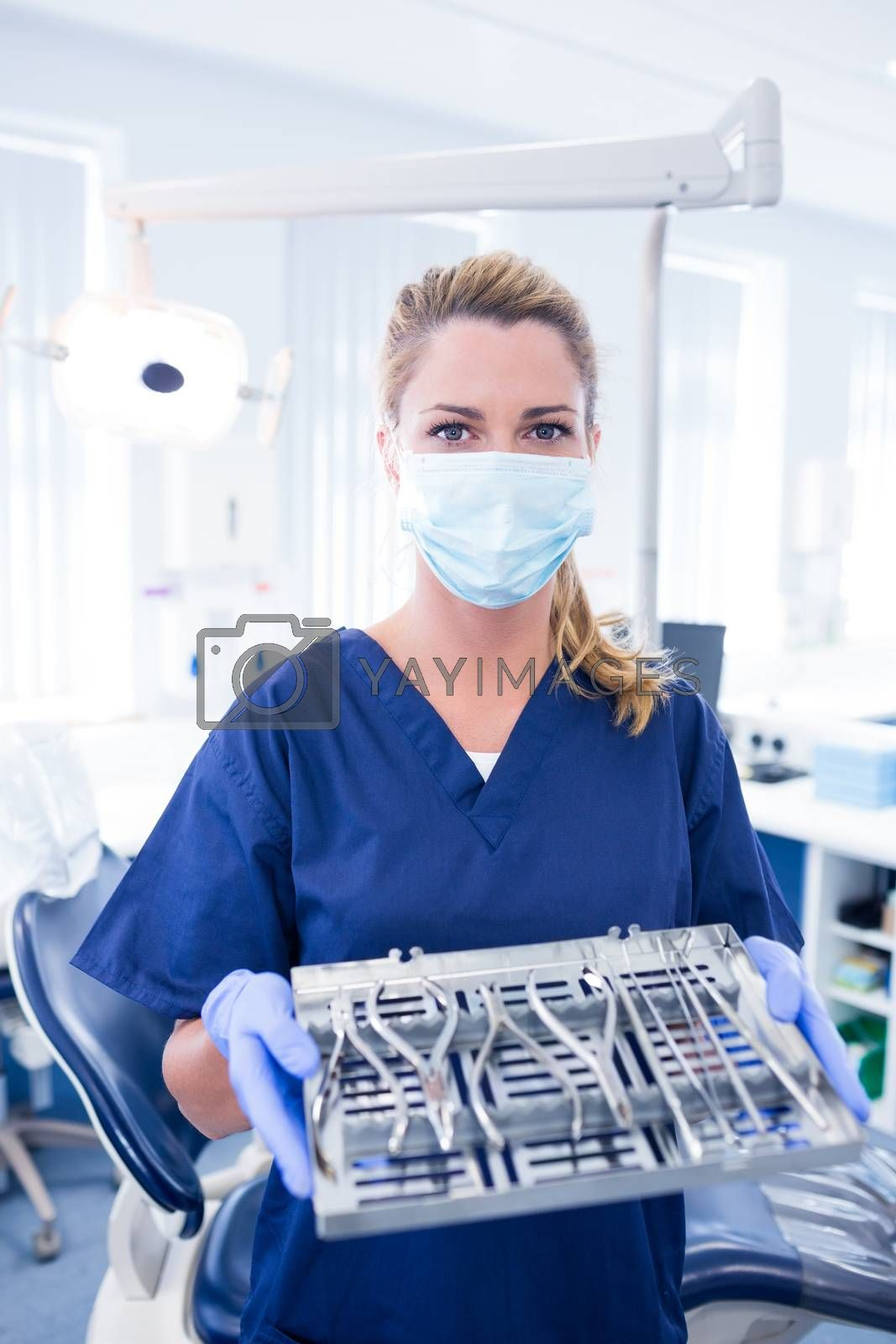 Dentist in blue scrubs offering tray of tools at the dental clinic