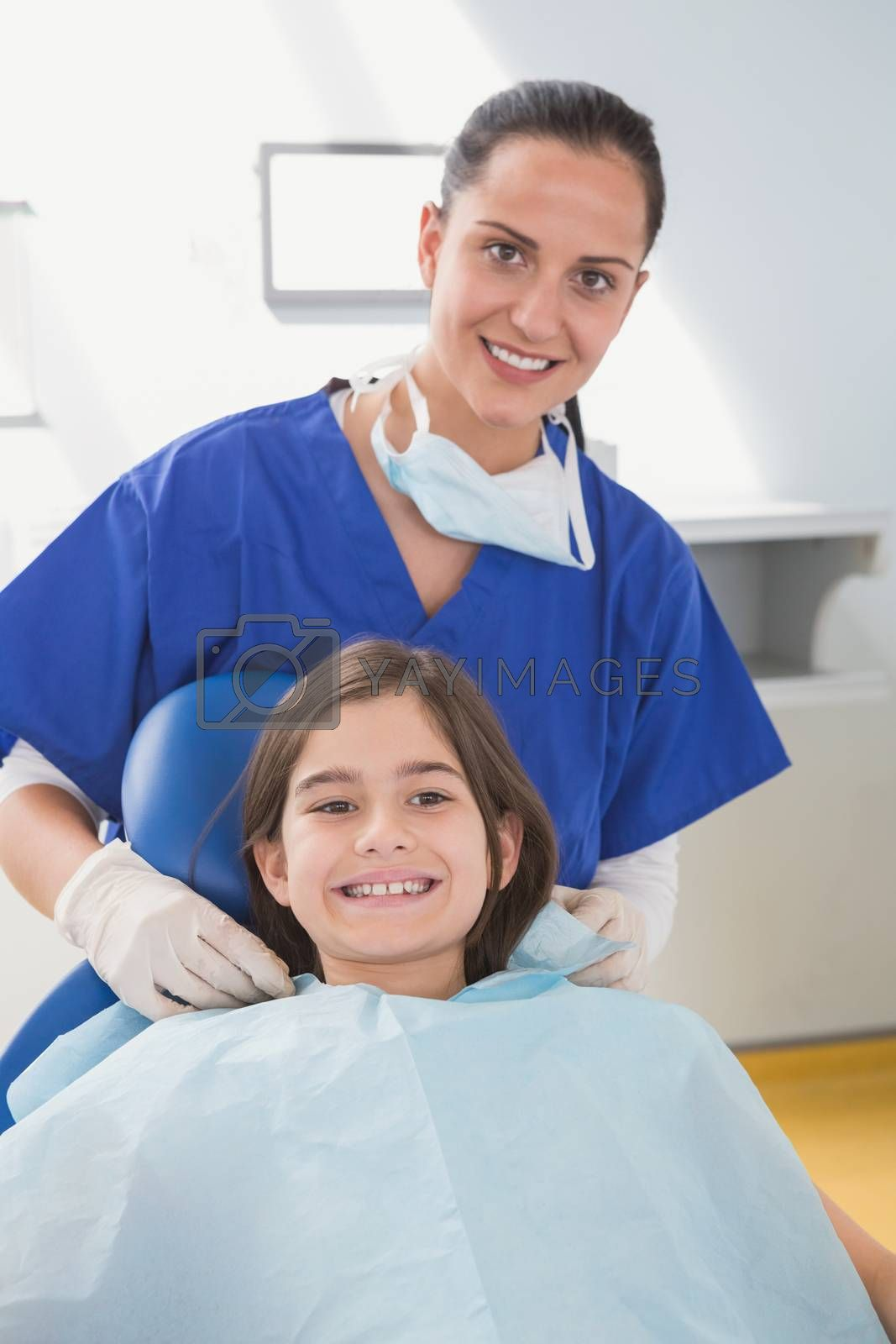 Pediatric dentist putting on her young patient the scrubs in dental clinic