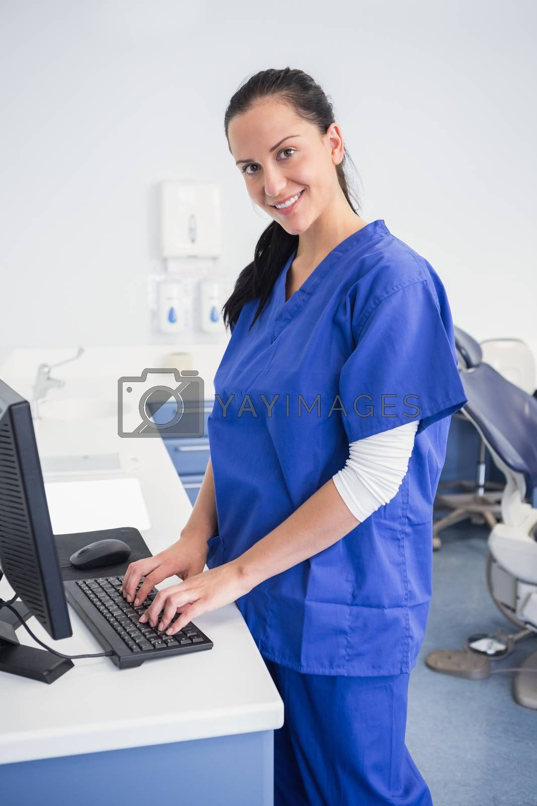 Smiling dentist typing on keyboard in dental clinic