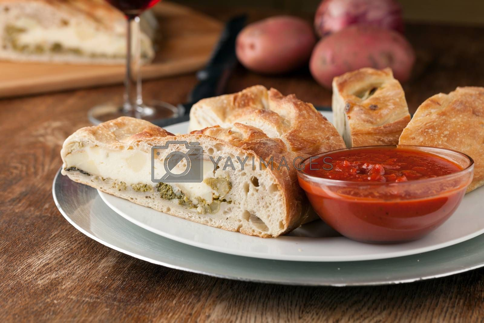 Homemade stromboli or stuffed bread with broccoli potatoes garlic onions and mozzarella cheese along with a side of marinara dipping sauce.
